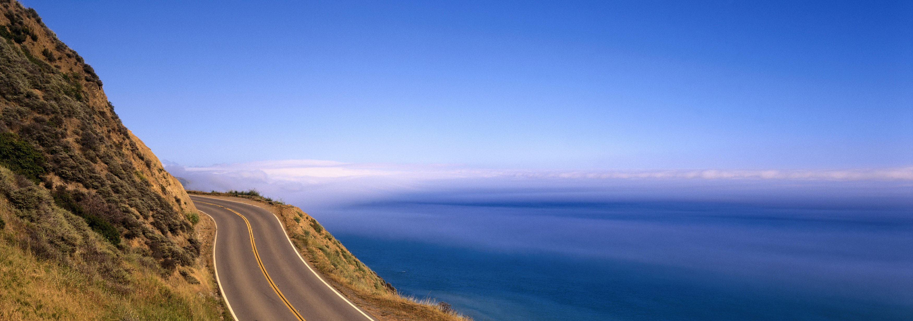 click to free download the wallpaper--nature scenes - The Incredibly Blue Sea and Sky, a Narrow and Straight Road 3500X1234 free wallpaper download