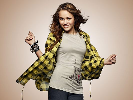 click to free download the wallpaper--A Popular Recording Artist, She is the Star of the Last Song, Happy and Excited Her on a Light Orange Background - HD Miley Cyrus Wallpaper