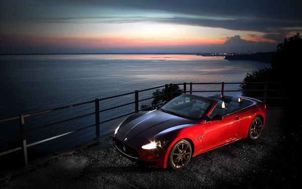 click to free download the wallpaper---A Red Maserati Car by Beachside, Lights Are Still on, Engine Should Not be Started, Never Weaken the Sea up - Maserati Cars Wallpaper