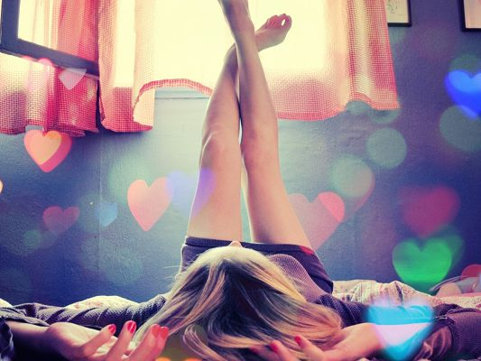 Adorable Girls Image, Young Girl Lying on Bed, Legs Swinging, Hearts Flying Around