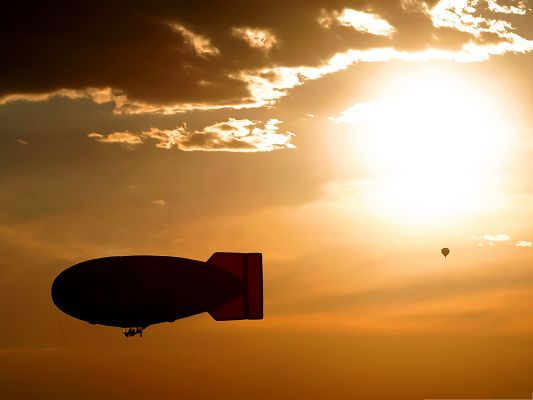 click to free download the wallpaper--Airships Wallpaper, Small Airship in the Golden and Bright Sky