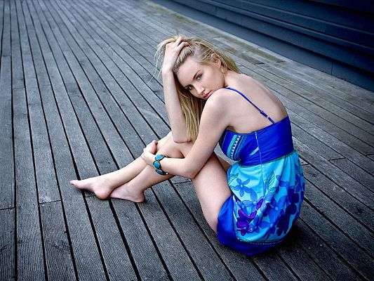 click to free download the wallpaper--Amazing TV Show Pic, Blonde Beauty in Blue Dress, Sitting on Plywood, Looking Back