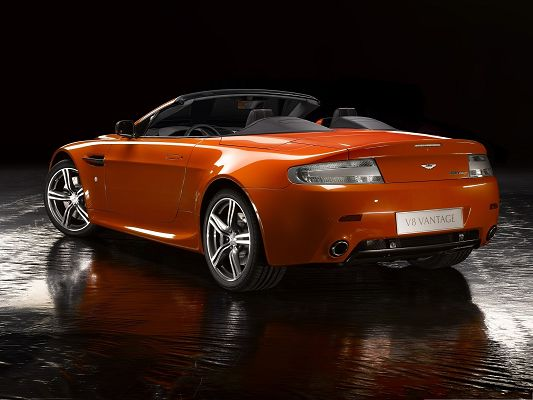 click to free download the wallpaper--Aston Martin Vantage as Background, Orange Super Car on Wet Road, Incredible Look