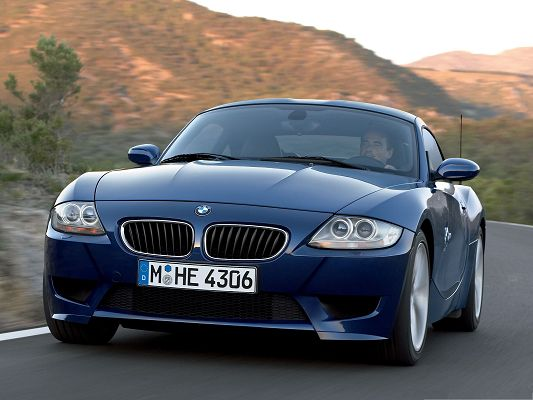 click to free download the wallpaper--BMW Z4 Coupe Car Wallpaper, Blue Super Car in Pretty Full Speed, Tall Hills Alongside