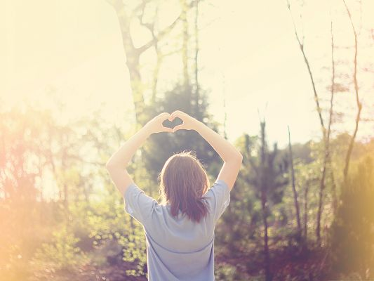 click to free download the wallpaper--Beautiful Girl Outdoor, Making a Heart Pose, Warm Sunshine Embracing Her