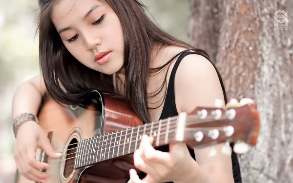 click to free download the wallpaper--Beautiful Girl Pic, Nice Girl Playing with Guitar, Serious Look