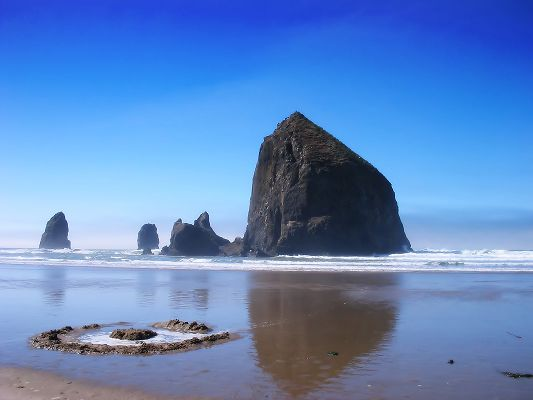 click to free download the wallpaper--Beautiful Image of Nature, Haystack Rock Under the Blue Sky, the Peaceful Sea