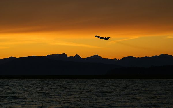 click to free download the wallpaper--Beautiful Image of Nature Landscape, an Outbound Plane, the Golden Sky, the Peaceful Sea