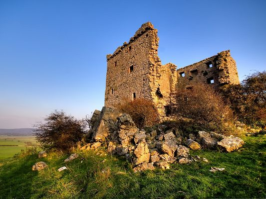 click to free download the wallpaper--Citadel Ruins Landscape, Standing Walls and Brown Stones, Under the Blue Sky