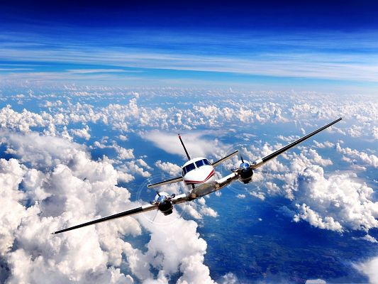 click to free download the wallpaper--Free Plane Wallpaper, Aircraft in Flight, White Spotted Clouds Beneath
