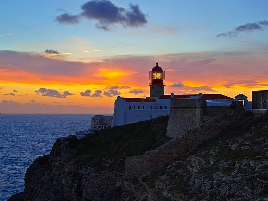 Image of Natural Landscape, Golden Lighthouse, the Setting Sun, the Peaceful Sea