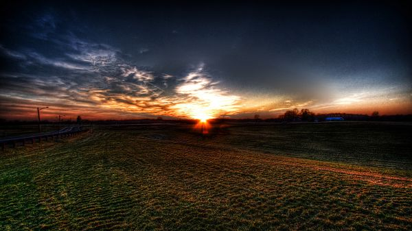 Images of Natural Scenes - The Setting Sun, a Field of Green Grass, the Sky is Getting Dark