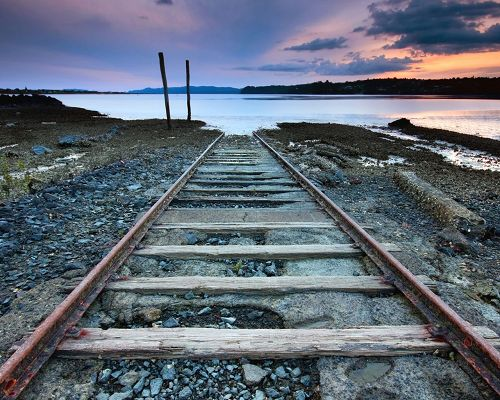 click to free download the wallpaper--Images of Natural Scenes, a Railway Leading to the Peaceful Sea, the Pink Sky, is Looking Good