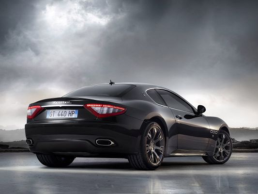 click to free download the wallpaper--Maserati Car Wallpaper, Black Super Car Turning a Corner, the Dark Sky