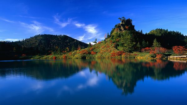 Natural Scenery pictures -  The Green Hills with Red Trees, Fully Shadowed in the Blue and Clear Sea