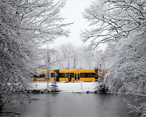 click to free download the wallpaper--Pics of Natural Scenery, a Yellow Train Among Snowy Scene, the Sea is Flowing, Hard to Believe