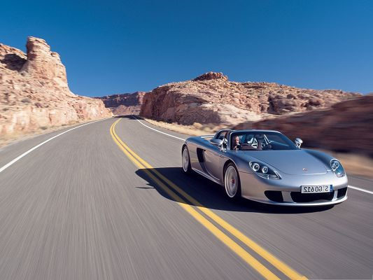 click to free download the wallpaper--Porsche Car as Wallpaper, Silver Car in Incredible Speed, Yellow Hills Alongside
