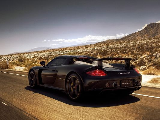 click to free download the wallpaper--Porsche Carrera GT, Black and Decent Car in the Run, Great Nature Landscape Alongside
