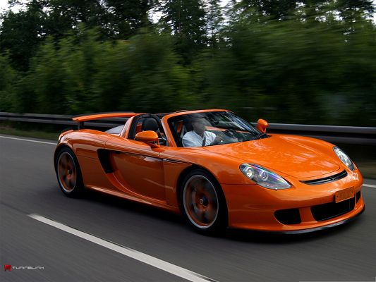 click to free download the wallpaper--Porsche Carrera GT Wallpaper, Orange Super Car in the Run, Incredible Speed