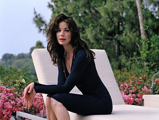 click to free download the wallpaper--Sitting on White Chair, in Dark Blue Dress, Surrounded by Various Flowers, She is More Beautiful and Attractive than Flowers - HD Michelle Monaghan Wallpaper