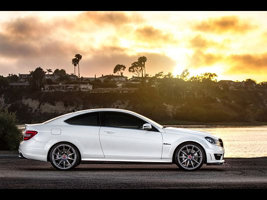click to free download the wallpaper--Super Car Images of Mercedes-Benz C63, a White Car in Front of the Sea, the Golden Sky