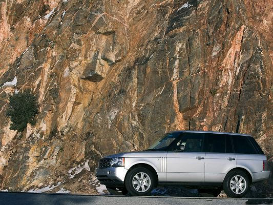 click to free download the wallpaper--Super Cars Picture, Range Rover Car Running Among Tall Yellow Stones