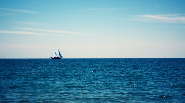 click to free download the wallpaper--natural scene photos - The Blue and Shinning Sea, a Boat on the Surface, Seems Endless