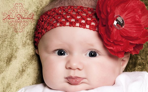 Wallpaper Of Super Baby: A Cute Baby With A Big Red Flower On Th Head