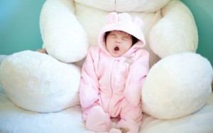 Wallpaper Of Baby: A Cute Pink Baby Yawning In The Hug Of Stuffed Bear